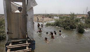 Toaleta w indyjskich slumsach, nieczystości wpadają wprost do wody, w której kąpią się dzieci