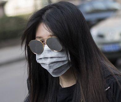 Chinka zakrywająca twarz maską podczas żółtego alarmu dotyczącego zanieczyszczenia powietrza w Pekinie