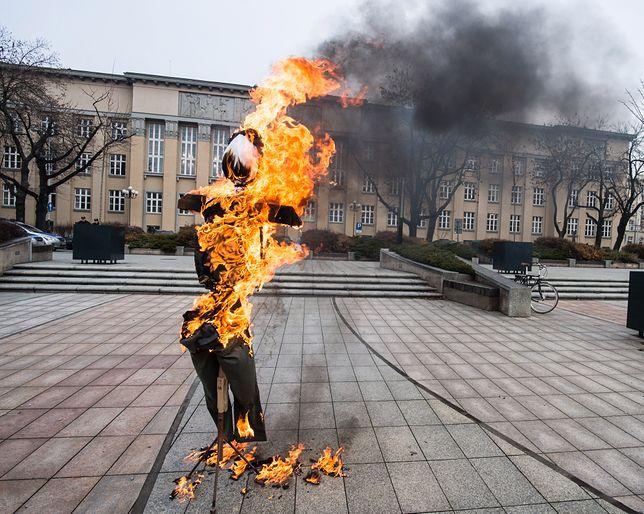 """Płonąca """"anonimowa"""" kukła przed siedzibą Sądu Okręgowego na placu Dąbrowskiego w Łodzi w ramach happeningu - to reakcja na wyrok 10 miesięcy więzienia dla Piotra Rybaka"""