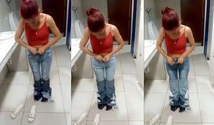 Kobieta na filmiku zdejmuje spodnie z siebie.