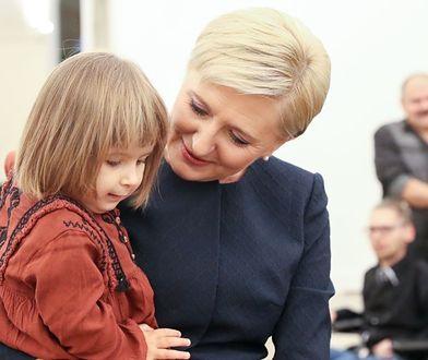 Agata Duda trzyma na rękach dziewczynkę chorą na rdzeniowy zanik mięśni