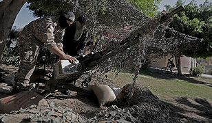 Członek Hamasu przygotowuje ciężki karabin maszynowy w Strefie Gazy