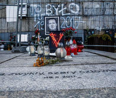 Znicze i kwiaty w miejscu samospalenia Piotra Szczęsnego w Warszawie