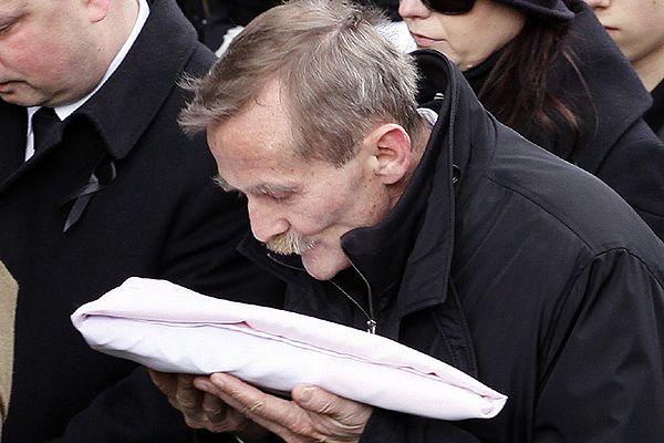 Ojciec Sebastiana Karpiniuka podczas pogrzebu syna z flagą, którą okryta była trumna - zdjęcie archiwalne
