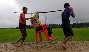Młodzi uchodźcy niosą kobietę przez granicę między Mjanmą i Bangladeszem