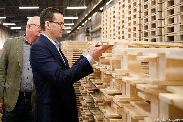 Mateusz Morawiecki ogląda europalety wyprodukowane w Zagnańsku