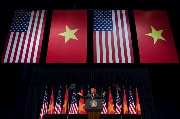 Barack Obama przemawiający na tle flag USA i Wietnamu w Hanoi