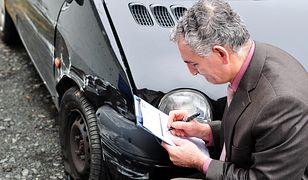 Rzeczoznawca robi wycenę szkody po stłuczce samochodu.