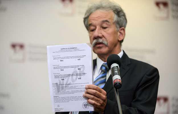 Wojciech Hermeliński prezentuje kartę do głosowania w referendum
