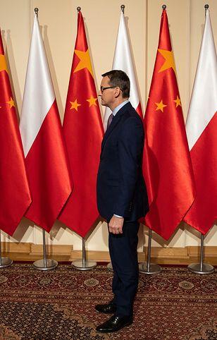 Premier Mateusz Morawiecki na tle flag polskiej i chińskiej.