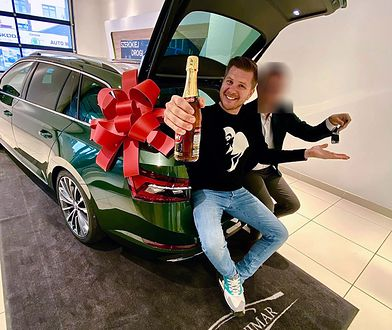 Filip Chajzer w bagażniku Skody Superb z bezalkoholowym szampanem