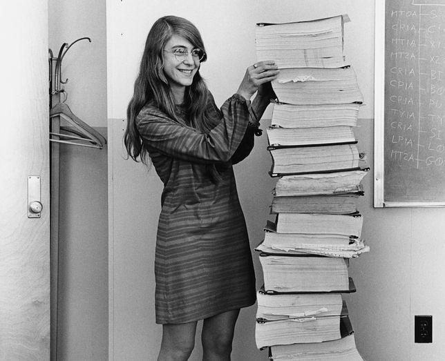 Margaret Hamilton obok zeszytów z kodem dla modułu dowodzenia i lądownika misji Apollo 11