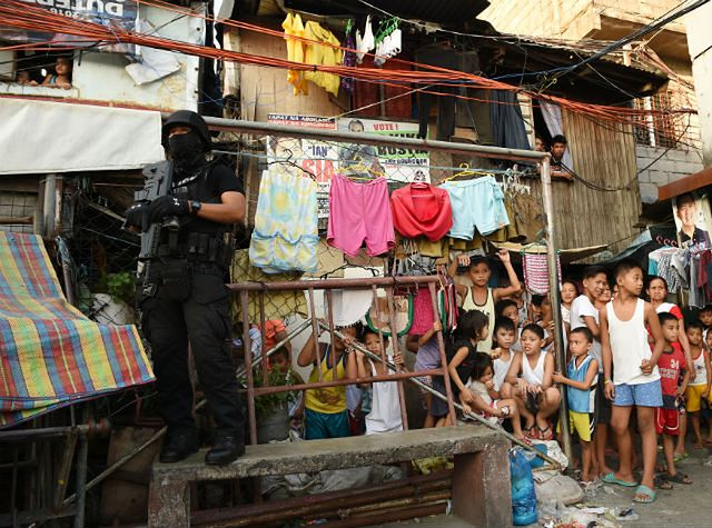 Policjant z oddziału specjalnego zabezpiecza teren podczas antynarkotykowej akcji w biednej dzielnicy Manili