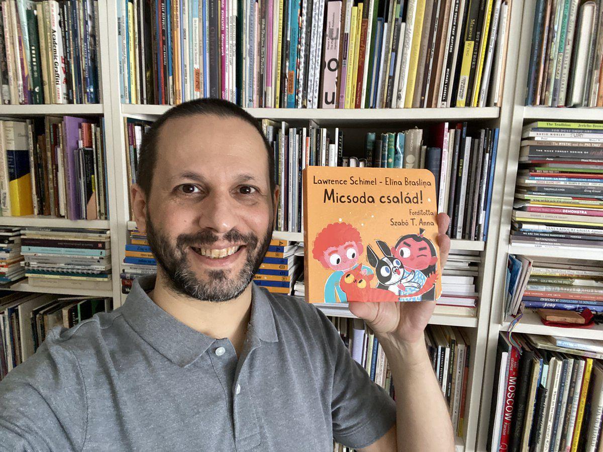 """Lawrence Schimel trzyma w ręku węgierskie wydanie swojej książki dla dzieci o """"tęczowej rodzinie""""."""