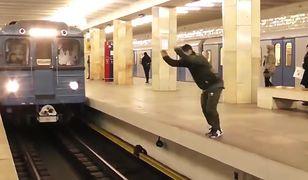 Mężczyzna wykonuje salto przed przejeżdżającą kolejką moskiewskiego metra.