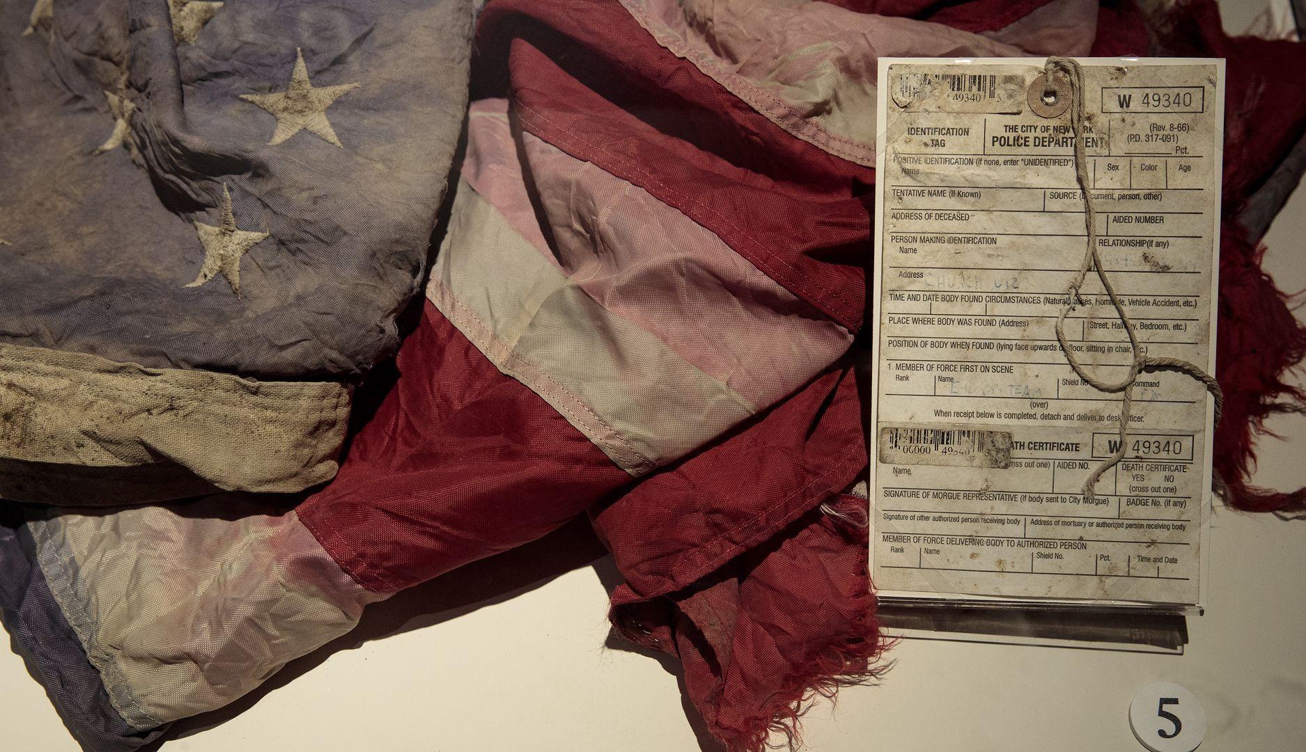 Flaga amerykańska wyciągnięta z ruin World Trade Center po zamachu Al-Kaidy 11.09.2001 r. Po prawej akt zgonu wydany przez nowojorską policję. Eksponat z muzeum poświęconego atakom