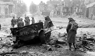 """Żołnierz z """"polskim"""" wykrywaczem min przy pojeździe wysadzonym przez minę we francuskiej miejscowości Tilly-sur-Seulles, 19 czerwca 1944 r."""