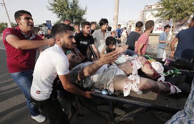 Uczestnicy wiecu transportują rannego w eksplozji