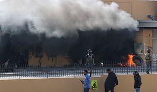 Irackie siły bezpieczeństwa stoją przy płonących oponach przy ambasadzie USA w Bagdadzie