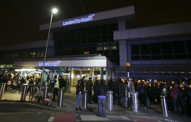 Pasażerowie przed budynkiem portu lotniczego