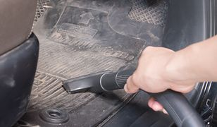 man cleaning his car with vacuum cleaner