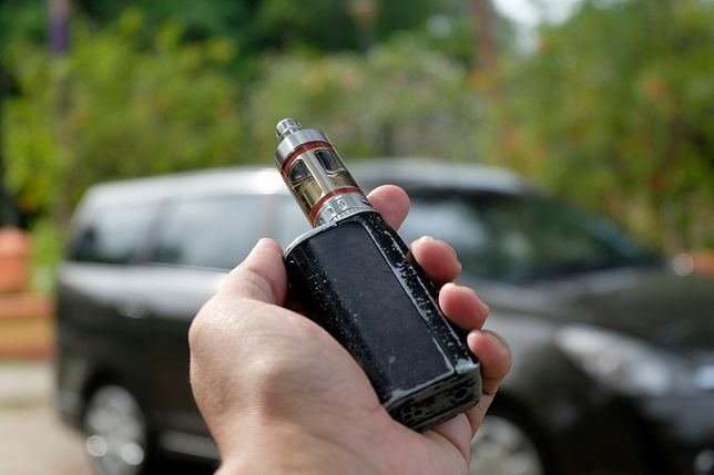 hand holding e-cigarette over blur background