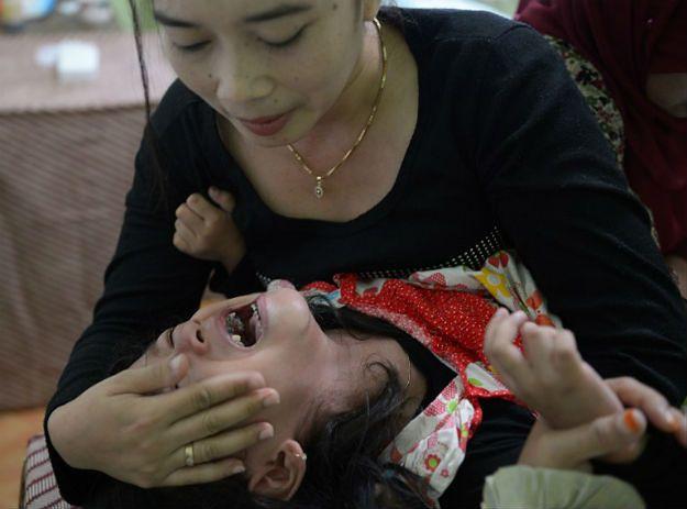 Indonezyjka próbuje uspokoić 4-letnią córkę, którą poddała zabiegowi obrzezania
