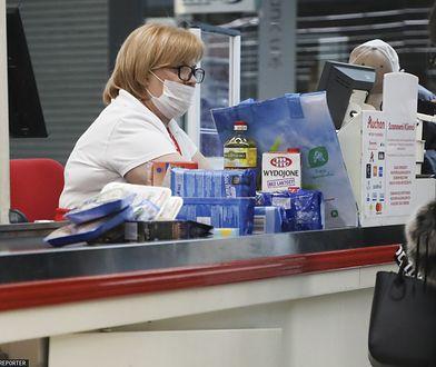 Kasjerka w ochronnej maseczce w supermarkecie w Krakowie