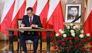 Premier Mateusz Morawiecki wpisuje się do księgi kondolencyjnej, wystawionej w KPRM po śmierci Jana Olszewskiego.