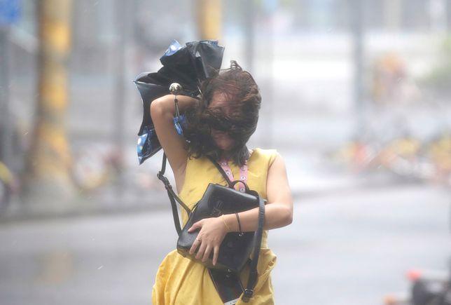 Kobieta na ulicy jednego z chińskich miast, w które uderzył tajfun