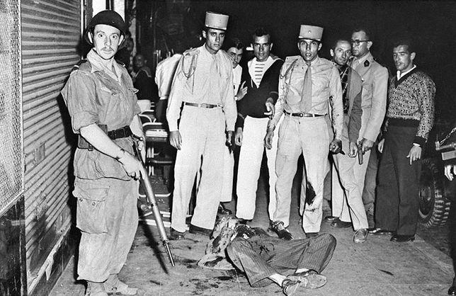 Żołnierz Legii Cudzoziemskiej (czwarty z prawej, z nożem w ręku) po zabiciu algierskiego partyzanta, który próbował wrzucić granat do restauracji. 15 października 1956 r.