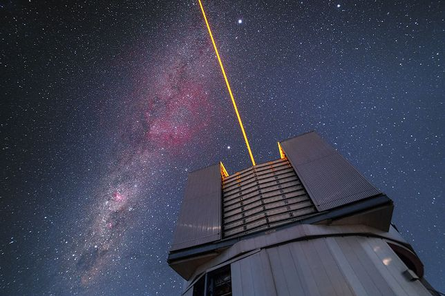 The VLT issue a laser into the sky over Paranal. The beam functions as an artificial star and is used to correct for atmospheric disturbance. The southern Milky Way crosses the sky, featuring the constellation of Carina among others.