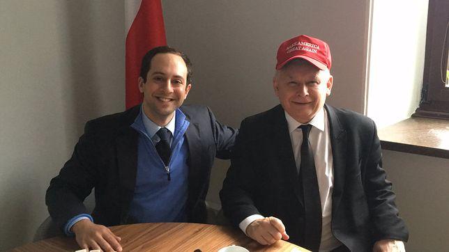 Uśmiechnięty Jarosław Kaczyński w czapeczce Donalda Trumpa