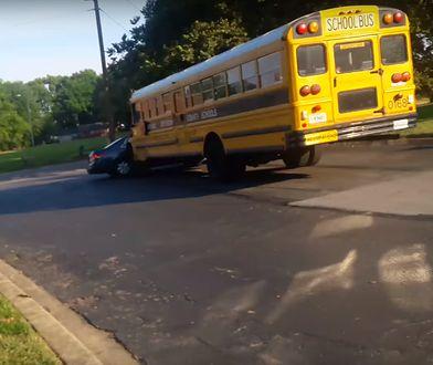 Autobus szkolny przepycha samochód na parkingu
