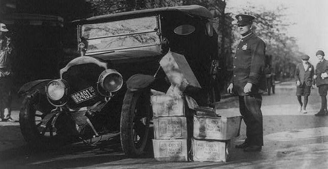 Amerykański policjant przy wraku samochodu i skrzynkach zarekwirowanego nielegalnego alkoholu, 1922 r.