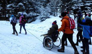 Grupka osób pomaga niepełnosprawnemu dostać się na Morskie Oko