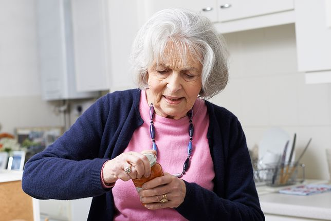 Senior Woman Struggling To Take Lid Off Jar