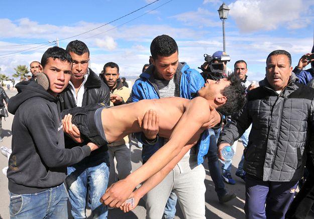 Protestujący trzymają kolejnego młodego Tunezyjczyka, który chciał popełnić samobójstwo podczas demonstracji; Al-Kasrajn, 22 stycznia