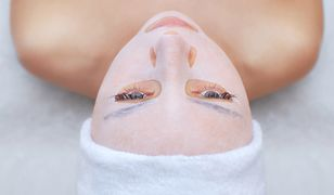 The cosmetologist for procedure of cleansing and moisturizing the skin, applying a sheet mask to the face of a young woman in beauty salon.Cosmetology and professional skin care.