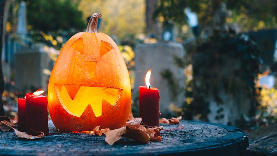 Halloween pumpkin Jack o lantern and candles on a graveyard.