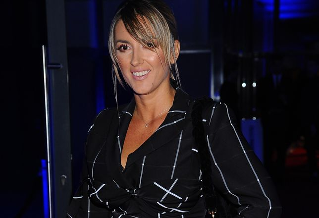 Karolina Szostak w brązowym garniturze. Spod marynarki wystała koronkowa bielizna