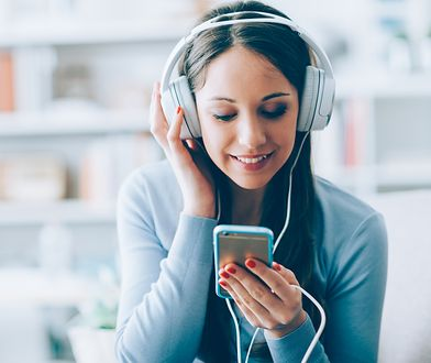 Smiling girl relaxing at home, she is playing music using a smartphone and wearing white headphones