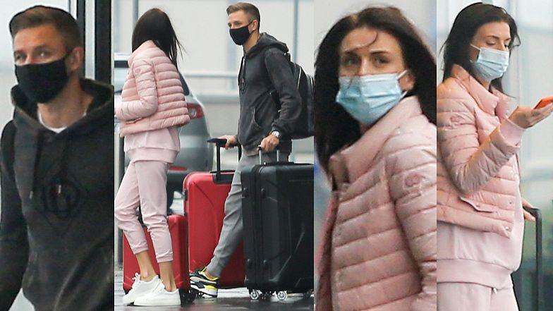 Obładowany bagażami Jakub Rzeźniczak na lotnisku z ciężarną Magdaleną Stępień