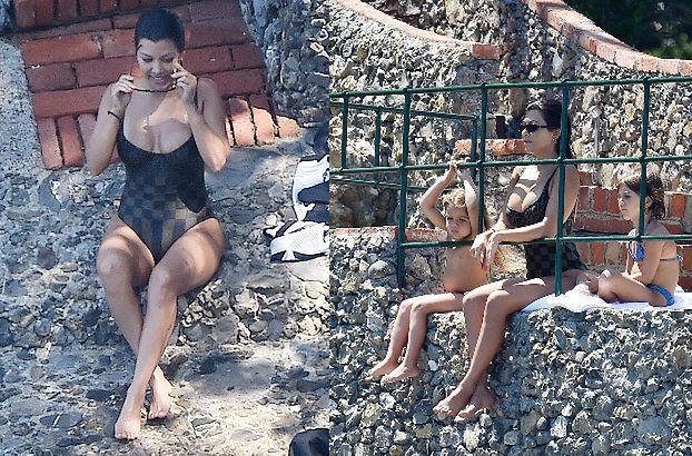 Ponętna Kourtney Kardashian wygrzewa się na portofińskiej skale w towarzystwie dzieci (ZDJĘCIA)