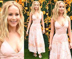 Zadowolona Jennifer Lawrence pozuje na tle butelek szampana
