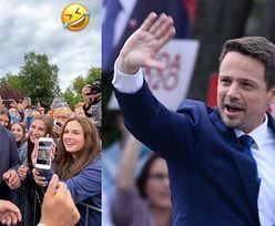 """Rozbawiony Rafał Trzaskowski spogląda na mema, na którym jest """"CIASTECZKIEM DO KAWUSI"""" (WIDEO)"""