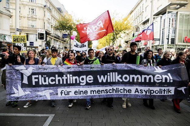 """Manifestujący trzymają baner z napisem """"Witamy uchodźców""""."""