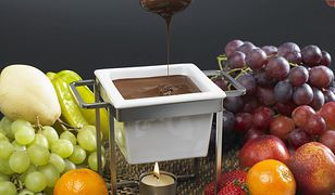 Owoc nabity na szpadkę lub długi widelec macza się w płynnej czekoladzie