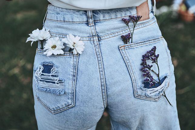 Luźne jeansy z szerszymi nogawkami i wyższym stanem mogą mieć lekkie przetarcia i dziury