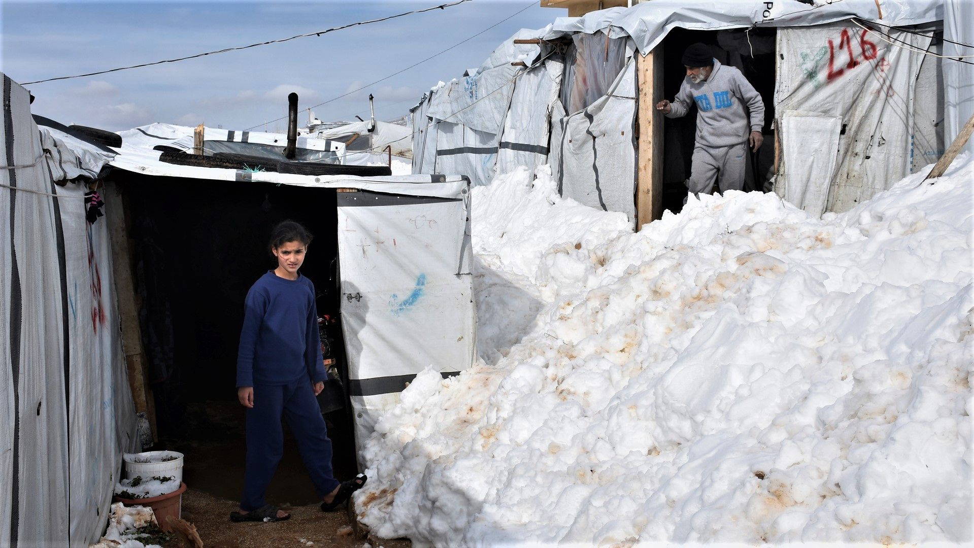 Mieszkańcy pokrytego śniegiem obozu dla uchodżców w Arsalu w Libanie